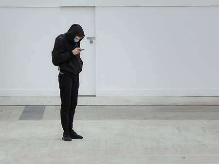 Kofler Soziale Distanz Digitale Nähe junger Mann mit Mundschutz Smartpone Covid-19 Corona-Krise