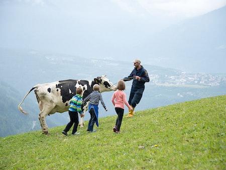 Bergbauer mit Kindern und Kuh auf der Weide