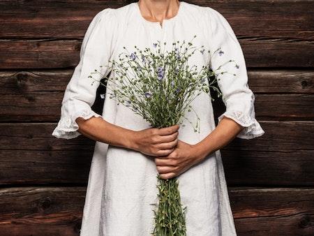 Frau in weissem Leinenkleid hält einen Strauss blau blühender Leinpflanzen
