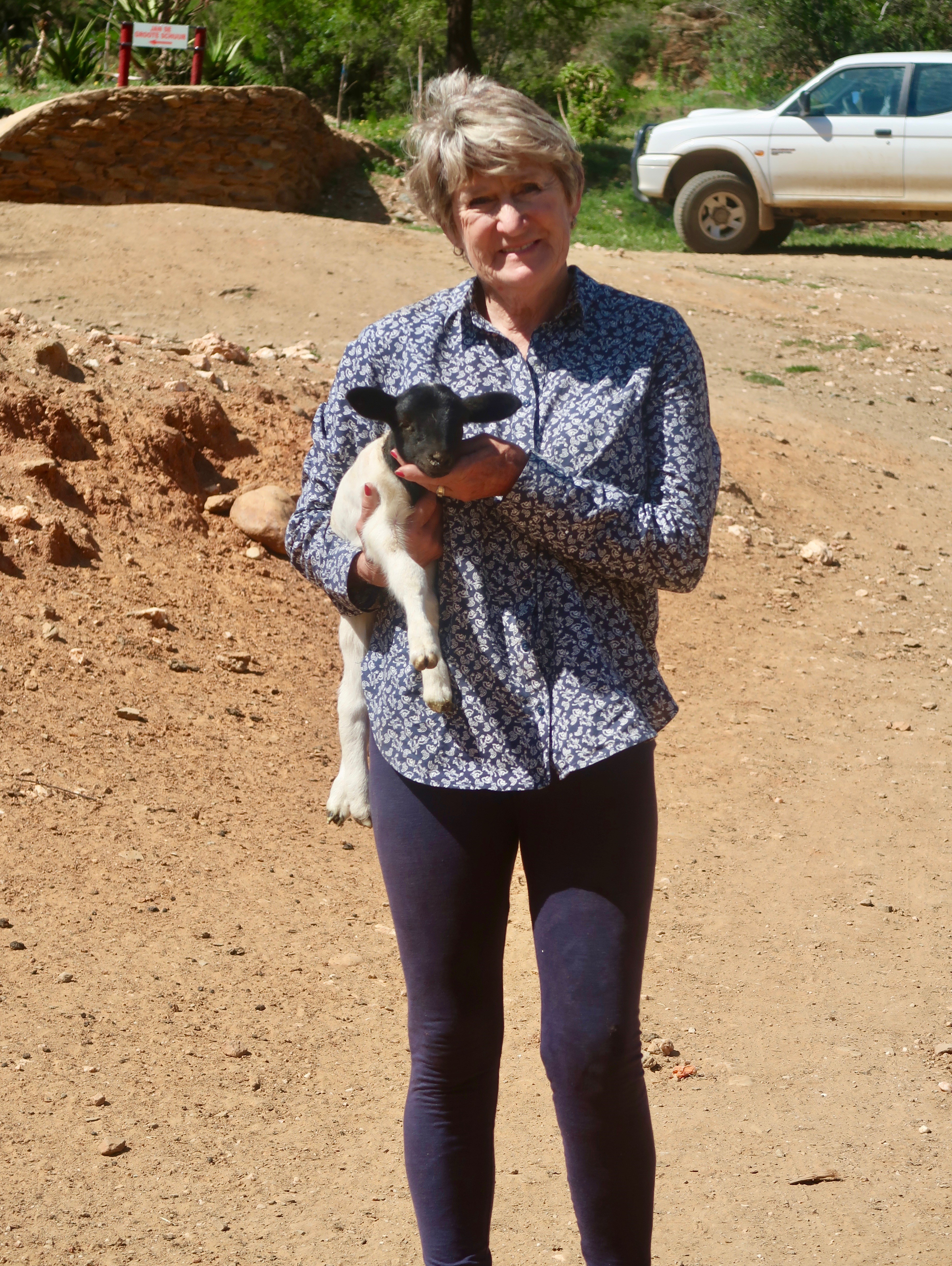 Maggie Fourie holding a lamb on the Oudemagurie farm